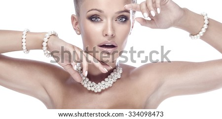 Beauty portrait of elegant blonde lady with creative hairstyle and perfect evening makeup. Woman wearing pearls. Studio shot.