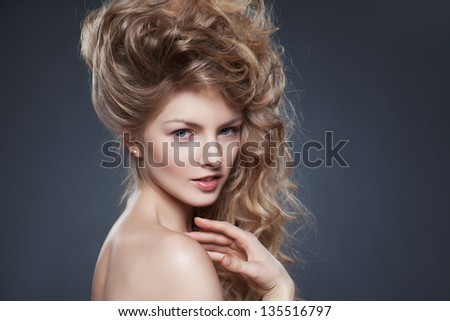 Beauty shot of young beautiful model with blond curly hair over grey background