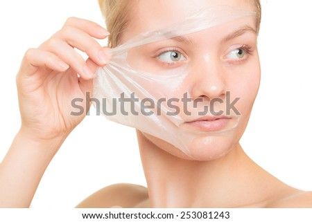 Beauty skin care cosmetics and health concept. Closeup young woman face, girl removing facial peel off mask isolated on white. Peeling