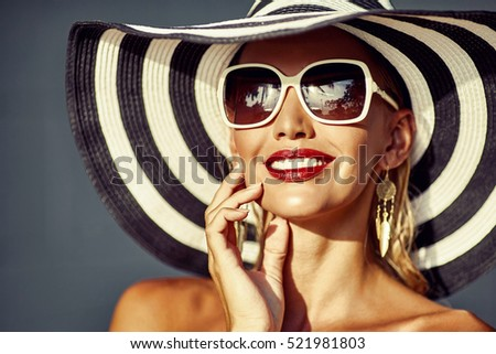 Beauty smiling young woman in hat and sunglasses - close up