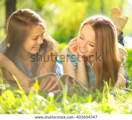 Beauty teen girls reading magazine and having fun outdoors. Beautiful joyful teenagers lying on spring grass, laughing and reading fashion magazine in spring park. Girlfriends outdoor. Friendship