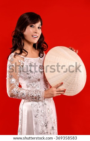 Beauty Vietnamese women wear traditional dress looking at camera with  Vietnamese hat in her hand