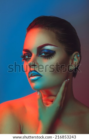 Beauty woman with make up and healthy skin in red and blue lights in studio