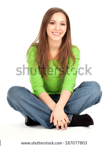 beauty young girl sitting on the floor with crossed legs, smiling, full lenght, white background
