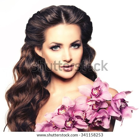Beauty young woman, luxury long curly hair with orchid flower. Haircut. Beautiful woman fresh healthy skin, makeup, lips, eyelashes. Fashion model in spa care salon. Sexy trendy hairstyle look.