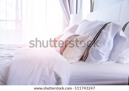 bed maidup with clean white pillows and bed sheets in beauty room close
