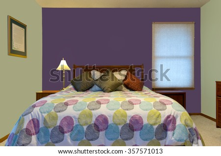 bedroom interior with purple and green walls lamp colorful pillows and comforter decorating queen size bed
