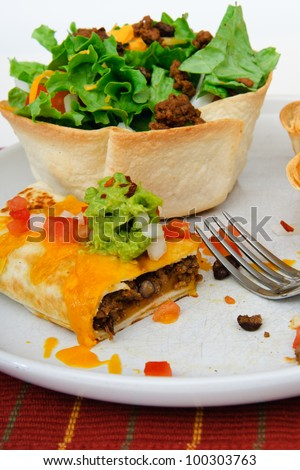 Beef and bean burrito with cheddar cheese salsa guacamole taco salad and beer