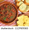 Beef chili with tortilla chips and garlic bread. - stock photo
