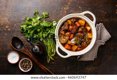 Beef meat stewed with potatoes, carrots and spices in ceramic pot