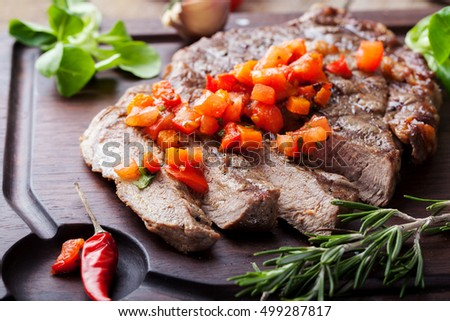 Beef steak well done with tomato and pepper salsa on a wooden background