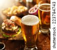 beer and burgers on wooden table - stock photo