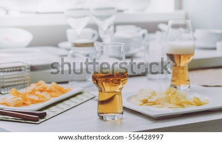 Beer and chips on the large white table. Restaurant