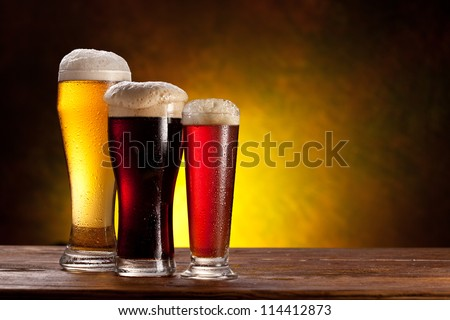 Beer barrel with beer glasses on a wooden table. The dark background.