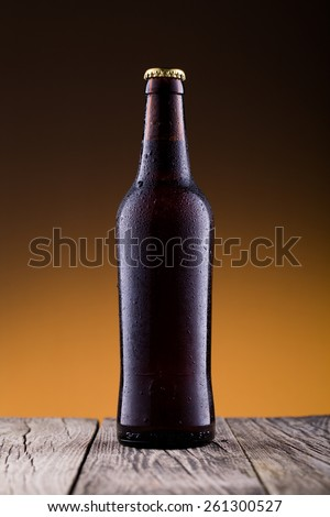 Beer bottle with water drops on a wooden table