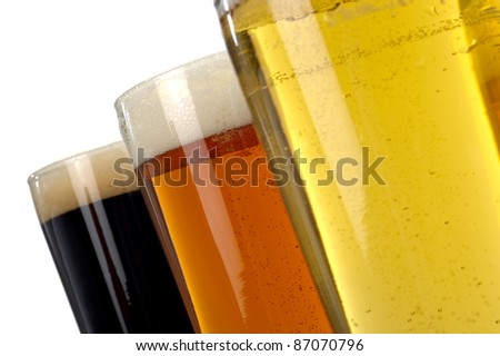 Beer decisions.  Colorful assortment of three beers shot on a white background.