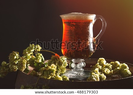 Beer in an antique etched glass tankard sitting on barrel with hops