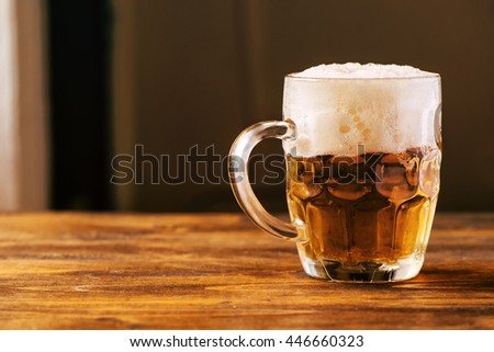 Beer mug full of cold fresh alcohol drink on wooden background, selective focus