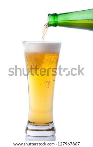 Beer pouring from bottle into glass on white