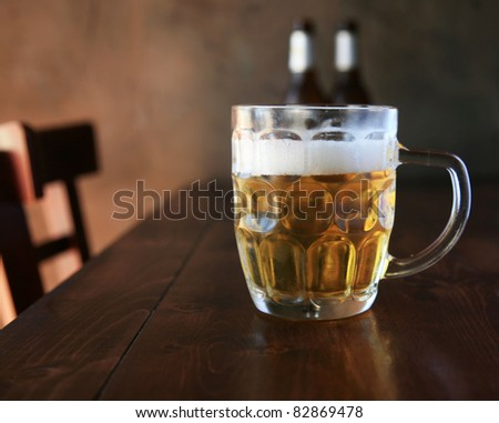 Beer. What more can I say?  Fresh been in a mug on a wooden table with a nice dark wall as a background in a restaurant on hot summer day.
