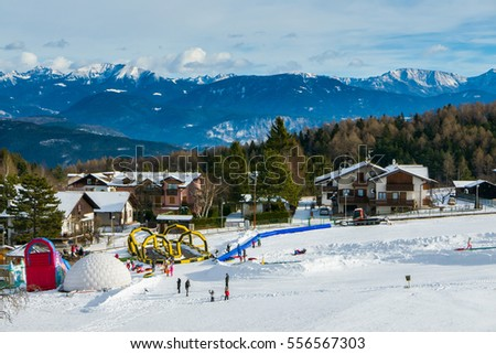 Beginners run for children and parents in ski resort with mountains in background