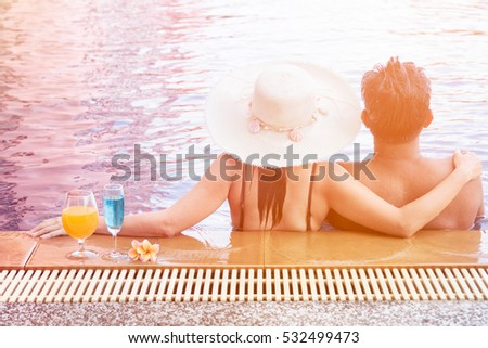 Behind of romantic Asian couple relaxing in the swimming pool,relax on vacation