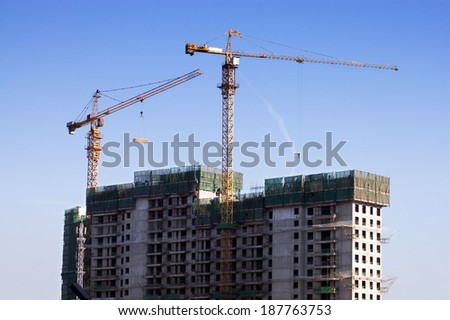 Beijing-November 11,2008: High-rise building construction site with cranes against blue sky