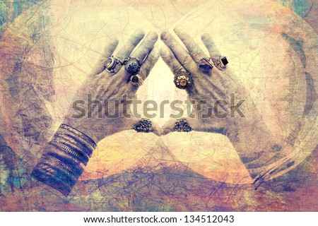 Bejeweled male hands opened from prayer into a frame of light.