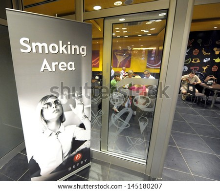BELGRADE, SERBIA - CIRCA JULY 2009: Travelers sits in smoking area cafe at Nikola Tesla airport circa July 2009 in Belgrade - stock photo