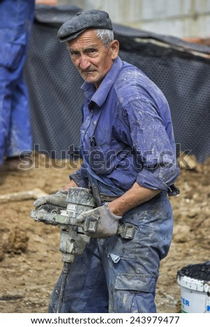 BELGRADE, SERBIA - MAY 24: Worker using paddle electric mixer for mix up the compound. At construction site in May 2014.