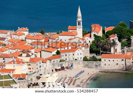 Bell tower of the Old Town of Budva city and Ricardova Glava beach. Aerial view with houses roofs. Adriatic sea. Montenegro