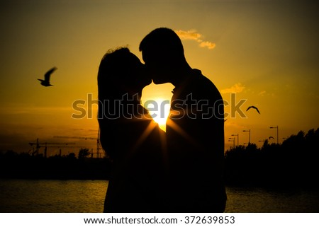 Beloved couple at the background of the warm evening sunset. Russia.