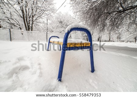 bench under snow on cold winter day