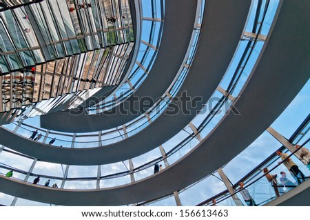 BERLIN, GERMANY - JUNE 08: people visit the Reichstag dome on June 08, 2013 in Berlin, Germany. It is a glass dome constructed on top of rebuilt Reichstag to symbolize the reunification of Germany.