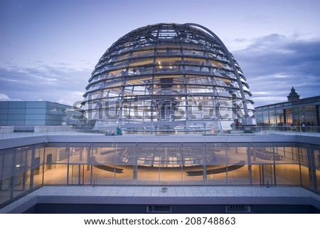 BERLIN, GERMANY - NOV 5: People visit the Reichstag dome at the German parliament at sunset on November 5 2013 in Berlin, Germany. Over 20 million people visit the city every year.