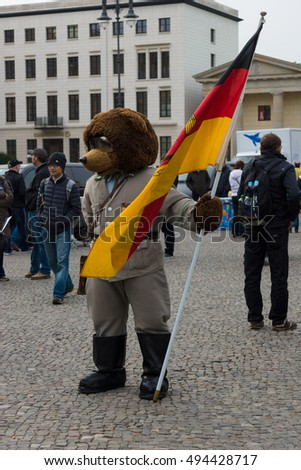 BERLIN, GERMANY - NOVEMBER 01, 2013: The Bear - a symbol of Berlin, in the uniform of soldier of the GDR on the background of the Brandenburg Gate.