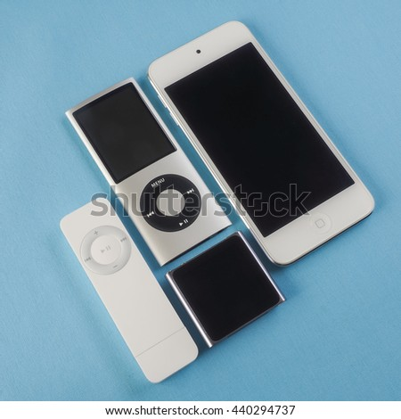 BERRY, AUSTRALIA - June 20 2016 : A group of Apple iPods - iPod Nano 6th generation, iPod Shuffle 1st generation, iPod Touch 5th generation and iPod Nano 4th generation - on a plain blue background.