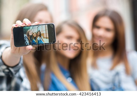 Best friends. Young friends girls are having fun together on the street and smile at each other. Funny and beautiful friends are doing selfie on cell phone