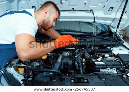 Best mechanic around. Handsome muscular car mechanic in uniform checking the engine in car service station