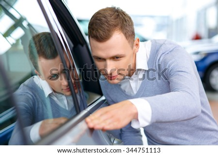 Best quality. Close up of pleasant positive man holding hand on the door of the car while choosing auto in auto show