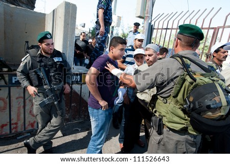 BETHLEHEM,  PALESTINIAN TERRITORIES - AUGUST 17: Israeli soldiers prevent a Palestinian from entering Jerusalem at the Bethlehem checkpoint on the last Friday of Ramadan, West Bank, August 17, 2012.