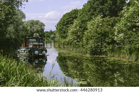 Beverley, Yorkshire, UK. A river boat sails down the beck (canal) on a calm, summer morning flanked by trees in bloom near Beverley, Yorkshire, UK.