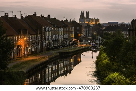Beverley, Yorkshire, UK. The Minster just after sunset with view of the beck (canal) flanked by modern town houses and barges with reflections in Beverley, Yorkshire, UK.