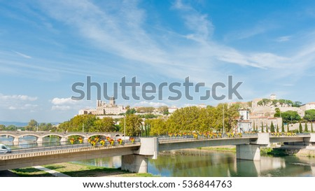 Beziers view across two bridges over Orb River to city and Cathedral Saint Nazaire, France.