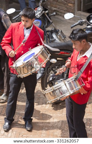 BHAKTAPUR, NEPAL, APRIL 24: Young Indian  musicians playing in the street of Bhaktapur during a traditional ceremony, Nepal, 2013.
