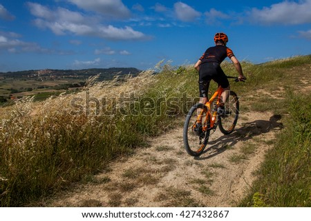 Bibbona, Tuscany, Italy - May 24, 2016: lifestyle using the mountain bike to ride in the paths of Tuscany and of the protected natural area of the Macchia Magona
