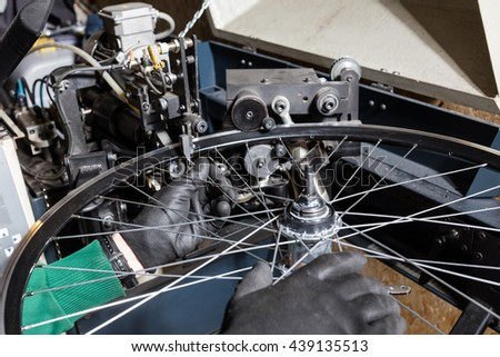 Bicycle service: mechanic serviceman installing spokes on wheel
