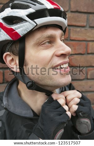 Bicyclist adjusting his helmet