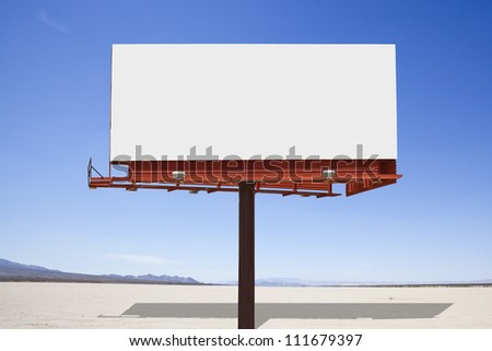 Big, blank billboard in the middle of a mojave desert dry lake.