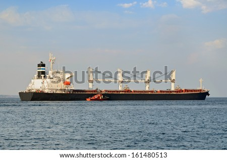 Big cargo ship with tugboat leaving sea port